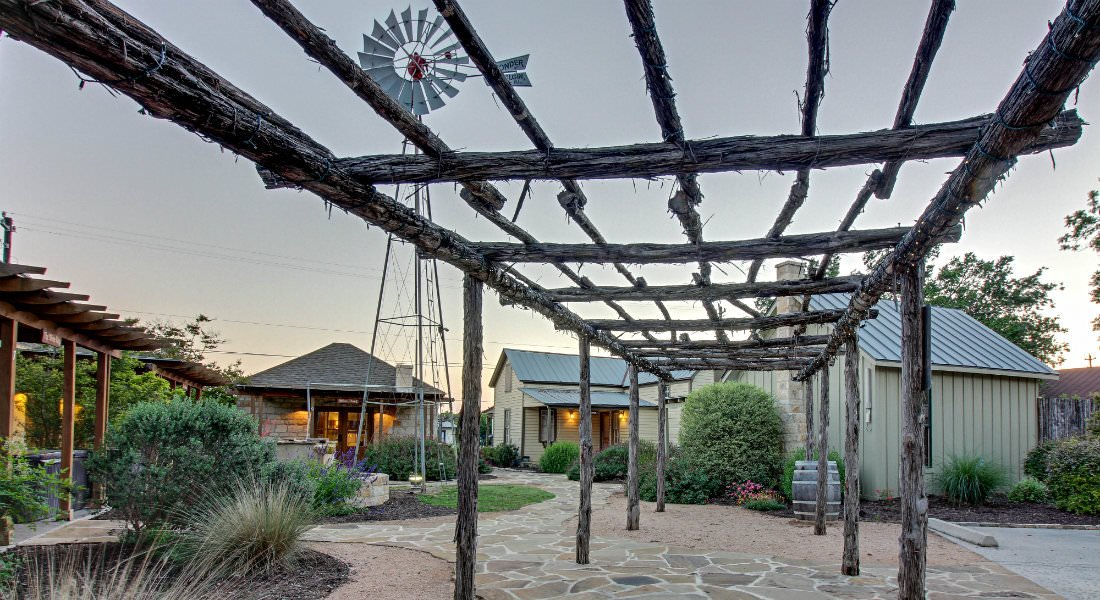 Outdoor view of property with rustic pergola, stone path, windmill, green shrubs and grasses