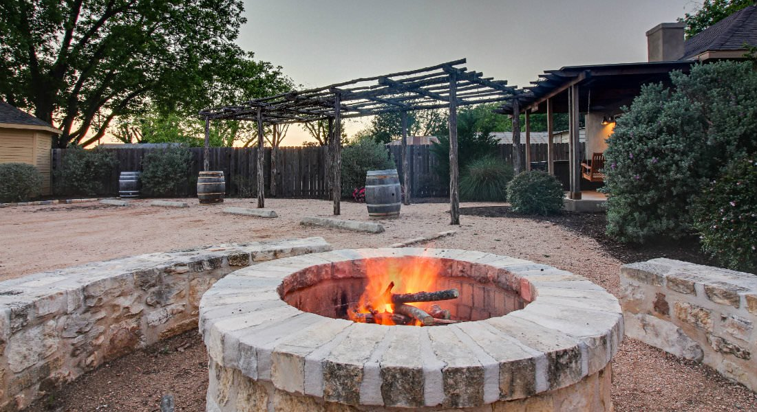Stone fire pit with fire surrounded by stone terrace with rustic pergola, wood wine barrels and trees in background