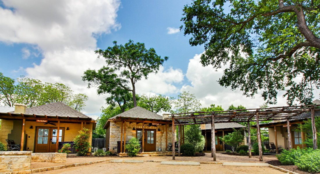 Outdoor view of cabins with rustic pergola, blue skies, white puffy clouds and green trees