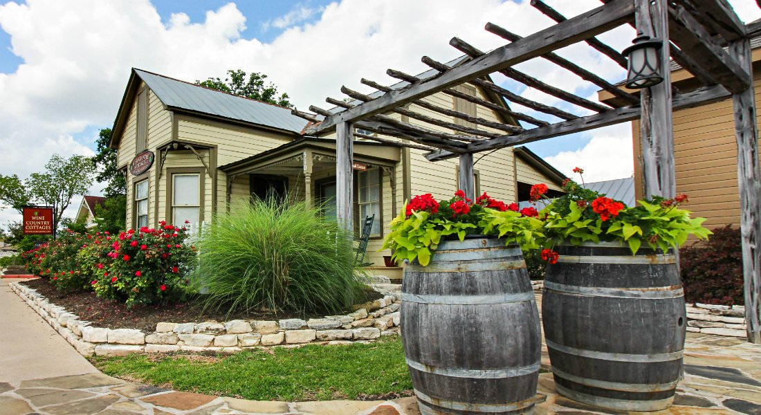 Tan cottage, stone terrace, brown mulch, flowering shrubs, ornamental grass, rustic pergola and wine barrels full of red flowers