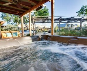 Bubbling hot tub in foreground with rustic pergola and green vines behind