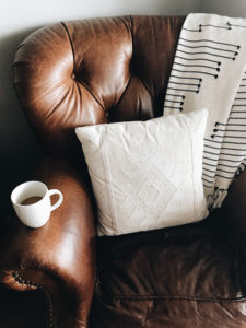 brown leather chair with white coffee cup on arm, white pillow and white & black throw on back