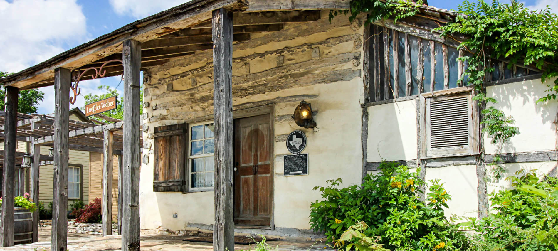 covered wooden porch and facade with brown door of historic Loeffler Weber Cabin
