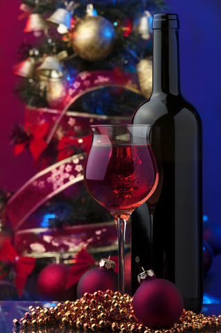 glass of red wine & wine bottle in front of Christmas balls and ribbons