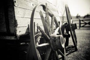 Black and white close up of wooden wagon wheels and wagon side with wooden fence in background