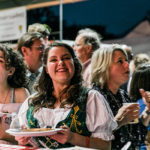 Smiling woman in green embroidered German dress, white blouse holding plate of food at Octoberfest, crowd of people behind