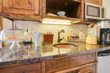 rustic wood cabinet kitchen with neutral granite and sink