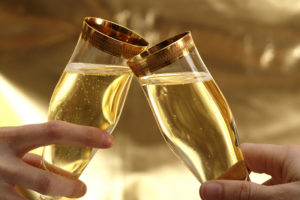 Two hands holding champagne glasses with gold rims making toast