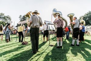 Group of tuba and euphonium players, some wearing lederhosen, standing on green lawn with backs to camera