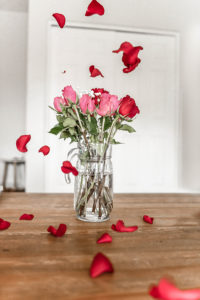 red rose petals falling from above around glass vase of pink and roses on wooden table