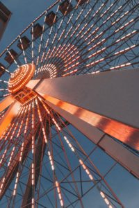 view from below of red ferris wheel at night with white and gold lights