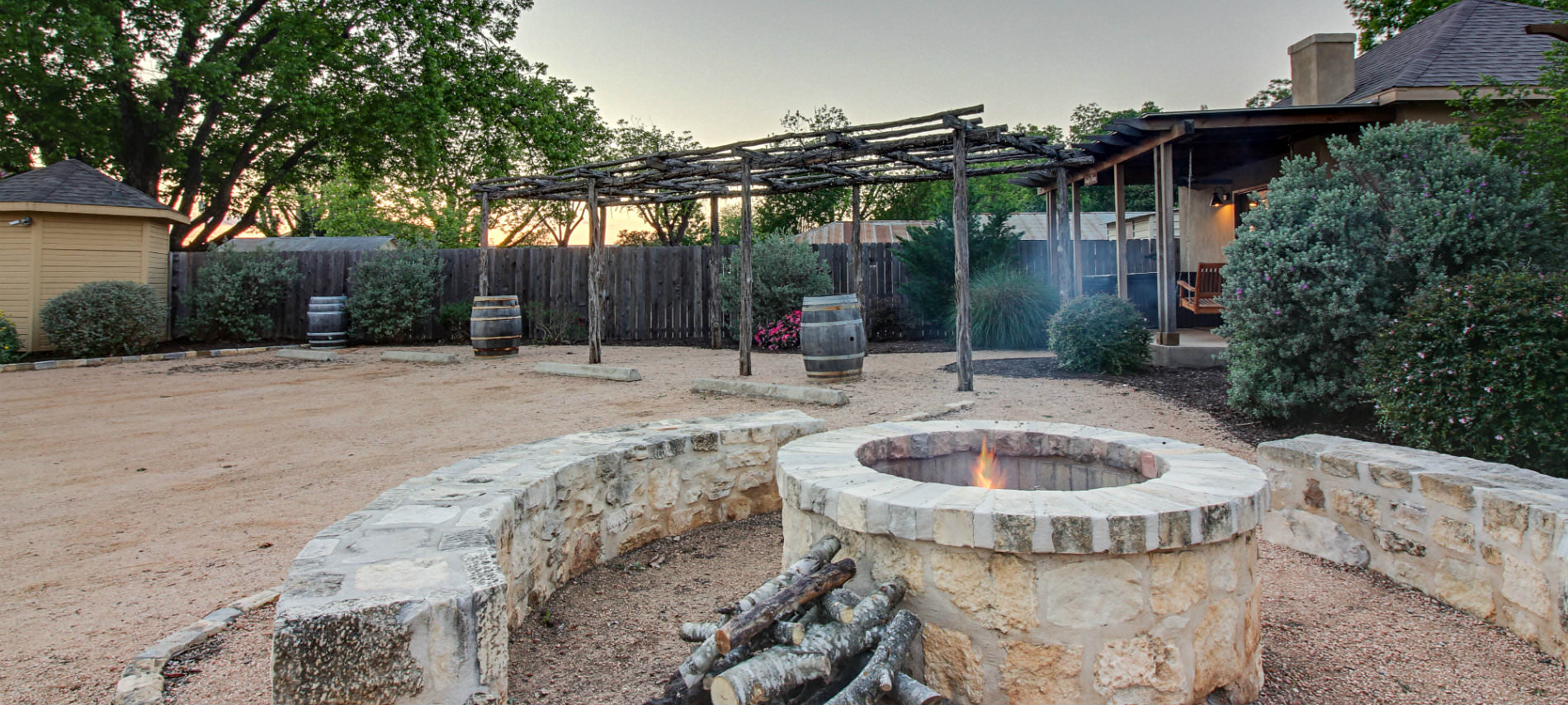 dessert looking common area with stone benches and fire pit with rustic pergola and cabing in background