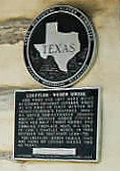 round black and gray Texas historic marker over square plaque