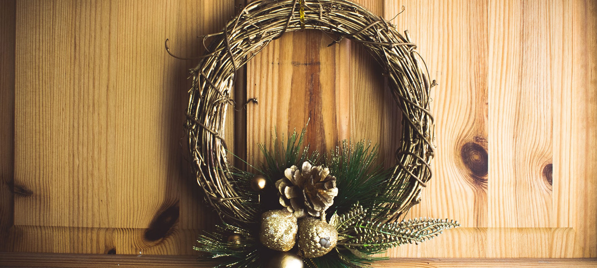 grapevine wreath with pine cones gold balls greens at bottom hanging on wood door