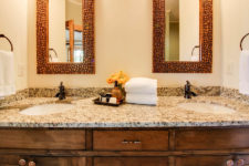 Rustic wood vanity with stone double bowl sink top, framed mirrors, bronze fixtures and towel rings with white towels