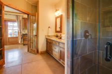 Ivory bathroom with stained concrete floors, tiled shower with glass door, wood vanity with stone top and glass French doors