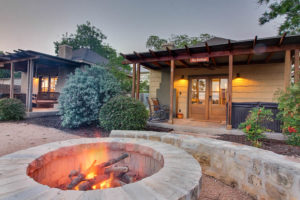 circular gray stone firepit in front of two rustic cottages with porches