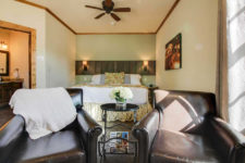 Ivory room with wood trim, ceiling fan, two brown leather chairs with black round table, and bed in the background