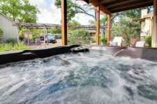 Bubbling water in hot tub under exposed beam porch with buildings and green trees in the background
