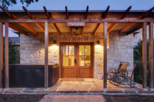 Stone rustic building, covered porch with exposed beams, hot tub, rocking chairs and stone slab and blue skies