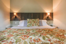 Bed with green and orange floral bedspread, round glass top nightstands, sconce lights and ivory walls