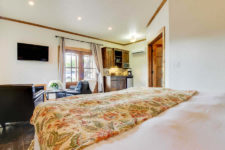 White room with stained wood trim, double window, fireplace with brown leather chairs, kitchenette and bed with floral quilt