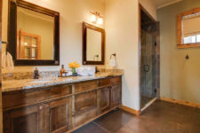 Rustic wood vanity with double bowl sinks, framed mirrors, stained concrete floors, tiled shower with glass door and small window