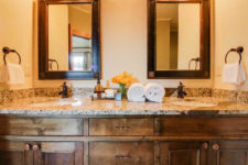 Rustic wood vanity with double bowl sinks, stone countertop, metal towel rings with white towels and framed mirrors