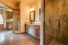 Ivory vaulted bathroom, stained pine trim, tiled shower with glass door and double sink vanity with mirrors and sconce lighting