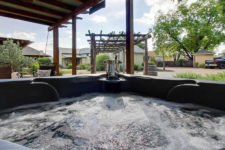 Bubbling water in hot tub with rocking chairs nearby and buildings and green trees in the background
