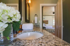 Stone double bowl sink top, oil-rubbed bronze fixtures, framed mirrors, sconce lighting and white flowers in glass vase