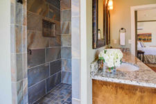 Gray and brown tiled walk-in shower, side view of wood vanity with double bowl stone sink top, bedroom in background