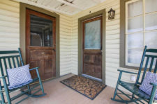 Covered porch with tan siding, brown trim, wood plank floor, two rustic wood and glass doors, two teal rocking chairs