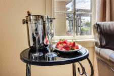 Small round black table topped with plate of fresh strawberries, two glass champagne flutes and a silver champagne bucket