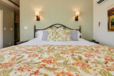 Light green and ivory walls, bed with metal scrolled headboard, green and orange floral quilt and sconce lighting