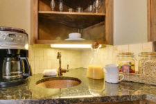 Kitchenette with beige tile backsplash, stone top with small round sink topped with coffee maker, orange juice, fruit and cereal
