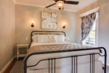 Beige walls, white trim, ceiling fan, window with black and white curtain panel, black metal bed, ivory nightstands, sconce lighting