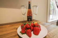 White plate of fresh red strawberries with two glass flutes and bottle of champagne on rustic wood plank table