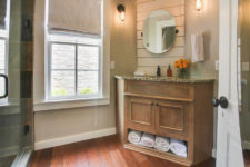 Beige bathroom with hardwood floors, rustic vanity with stone sink top, oval mirror, sconce lighting, white trimmed window with shade