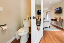 Ivory bathroom with white stool, hardwood floors and oval mirror on the door