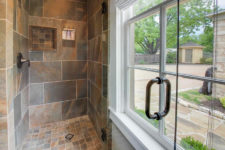 Tiled walk-in shower in shades of brown and gray with bronze fixtures, and a white trimmed window nearby