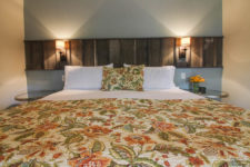 Close-up view of bed with white sheets, green and orange floral bedspread, round glass top nightstands and sconce lights
