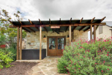 Outdoor view of stone cottage with double glass doors, exposed beam covered porch, stone slab, hot tube and flowering shrubs