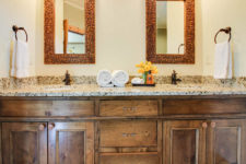 Close-up view of rustic wood vanity with stone double bowl sink top, framed mirrors, bronze fixtures and white towels