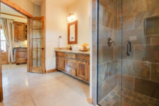 Large ivory bathroom with stained concrete floors, tiled shower with glass door, rustic wood vanity with double bowl sink