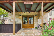 Stone cottage with exposed beam covered porch, double glass doors, stone slab and hot tub