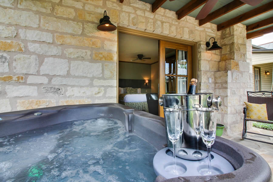 Stone cottage covered porch with hot tub full of bubbling water and two champagne flutes with champagne bucket