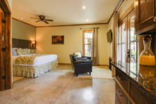 Spacious room with ceiling fan, stained concrete floors, bed with sconce lights, brown leather chairs and TV and kitchenette