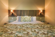 Close-up view of bed with leafy green bedspread, round nightstands and sconce lights