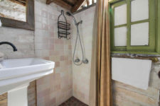 Rustic bathroom with pink and white tiled shower, white sink with oil-rubbed bronze fixture, and framed mirror